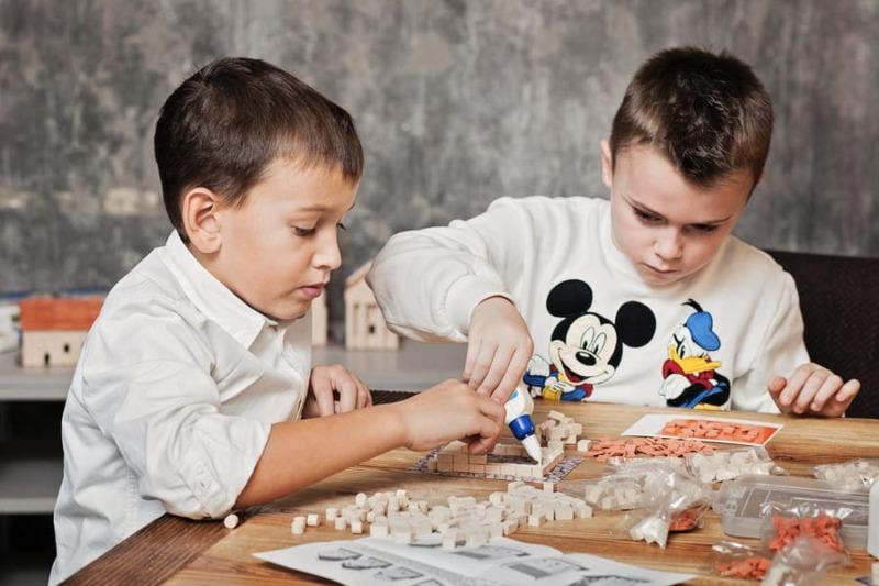 дети собирают керамический конструктор с маленьких кирпичиков