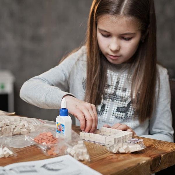девочка собирает керамический конструктор с мини кирпичиков