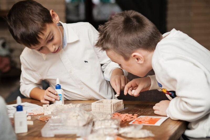 Мальчики собирают конструктор из мини кирпичиков